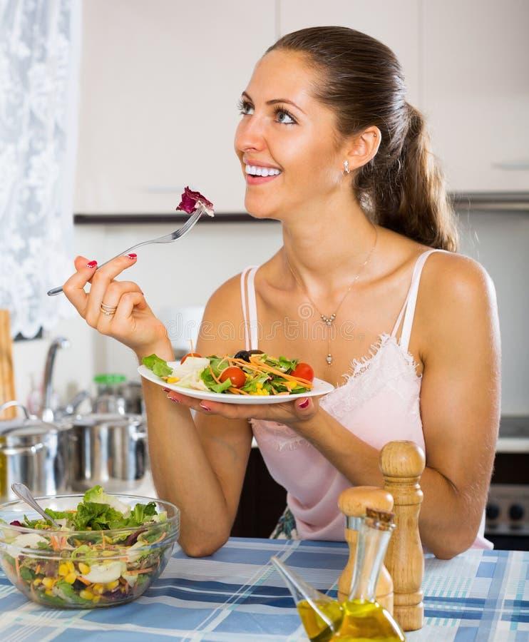 Ung kvinna som äter sallad på köksbordet arkivbilder