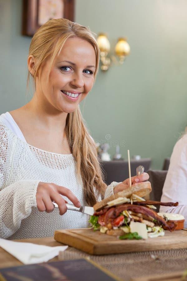 Ung kvinna som äter smörgåsen i restaurang arkivfoto