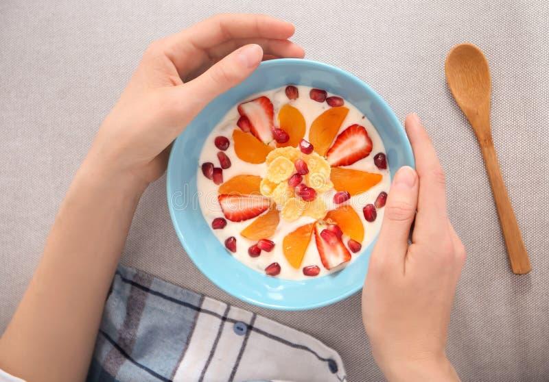 Ung kvinna som äter smaklig yoghurt med frukter royaltyfri fotografi
