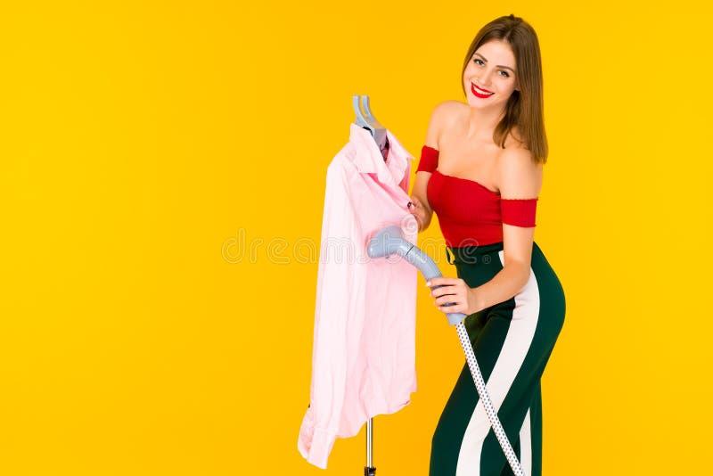 Ung kvinna som ångar den rosa skjortan på torr-rengöringsmedel arkivbilder