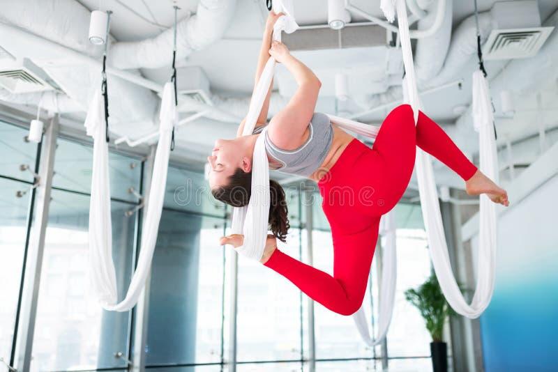 Ung kvinna som öva antigravity motiverad yogakänsla royaltyfri bild
