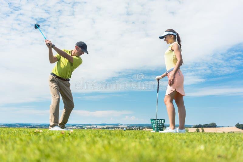 Ung kvinna som öva den korrekta flyttningen under golfgrupp med a arkivbild