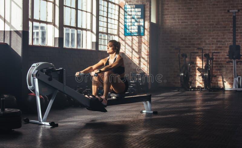 Ung kvinna som övar i gymnastiksal royaltyfria foton
