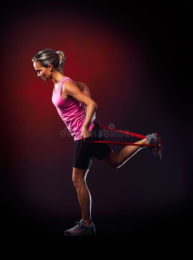 Ung kvinna som övar med den elastiska konditionmusikbandet i idrottshallen royaltyfri fotografi