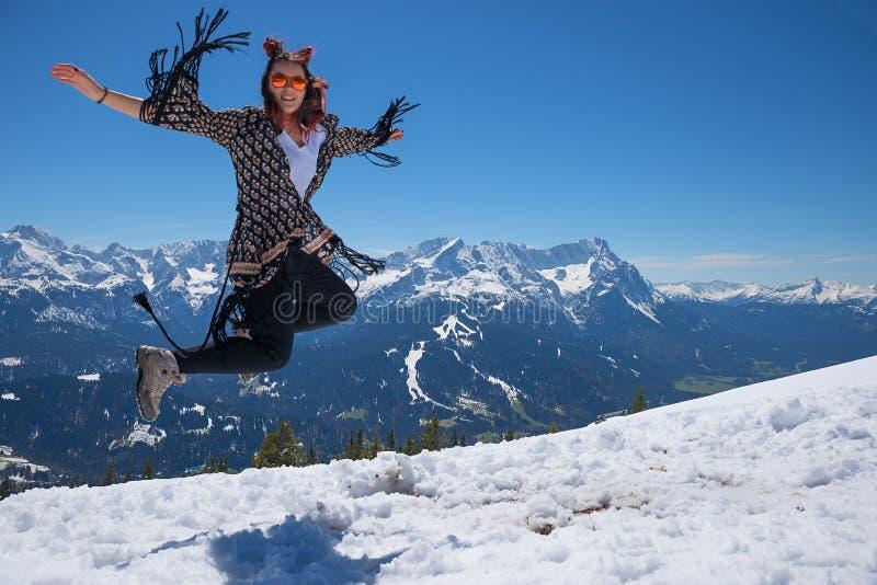 Ung kvinna som överst hoppar av berget i snöig landskap royaltyfri foto