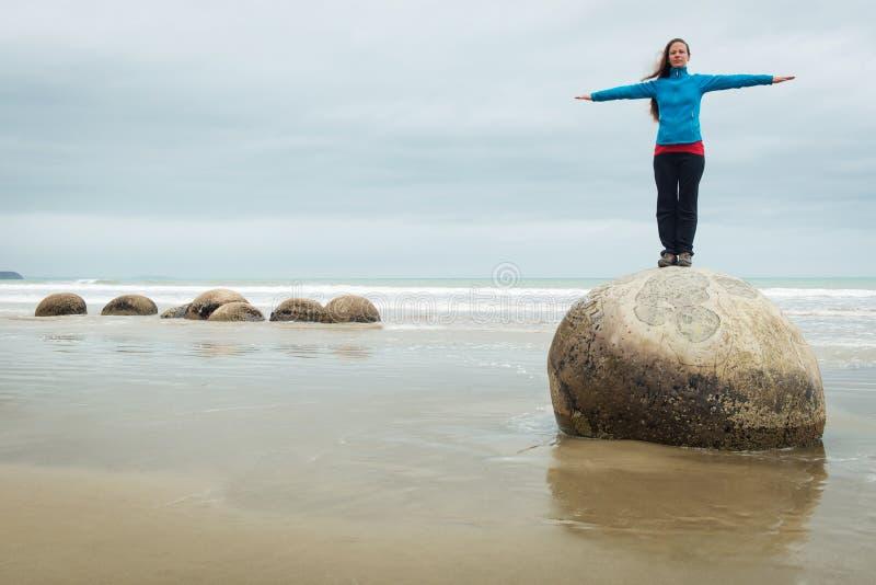 Ung kvinna som överst poserar av en Moeraki stenblock, Nya Zeeland arkivfoton