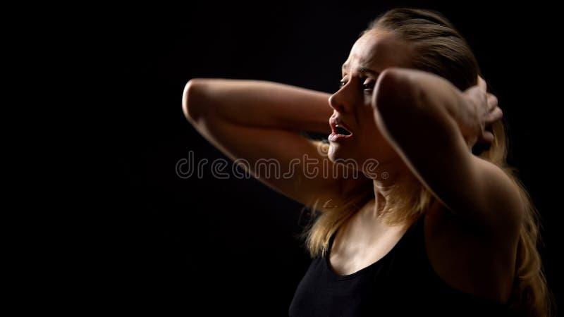 Ung kvinna som andas och skriker knappast mot mörk bakgrund, problem royaltyfria bilder