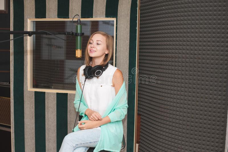 Ung kvinna som antecknar en sång i en yrkesmässig musikstudio royaltyfria foton