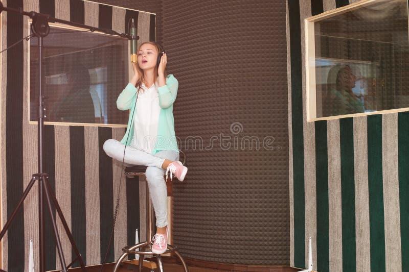 Ung kvinna som antecknar en sång i en yrkesmässig musikstudio fotografering för bildbyråer