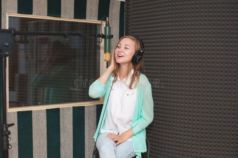 Ung kvinna som antecknar en sång i en yrkesmässig musikstudio royaltyfria bilder
