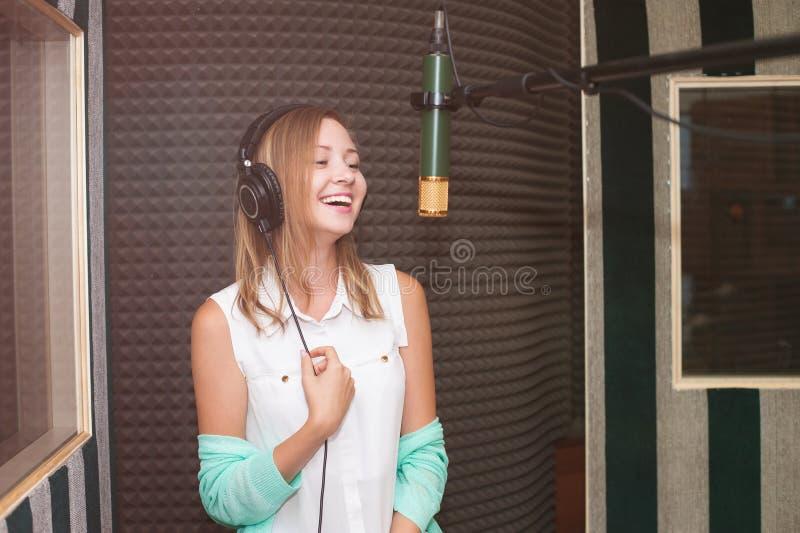 Ung kvinna som antecknar en sång i en yrkesmässig musikstudio arkivbilder