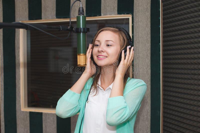 Ung kvinna som antecknar en sång i en yrkesmässig musikstudio arkivbild