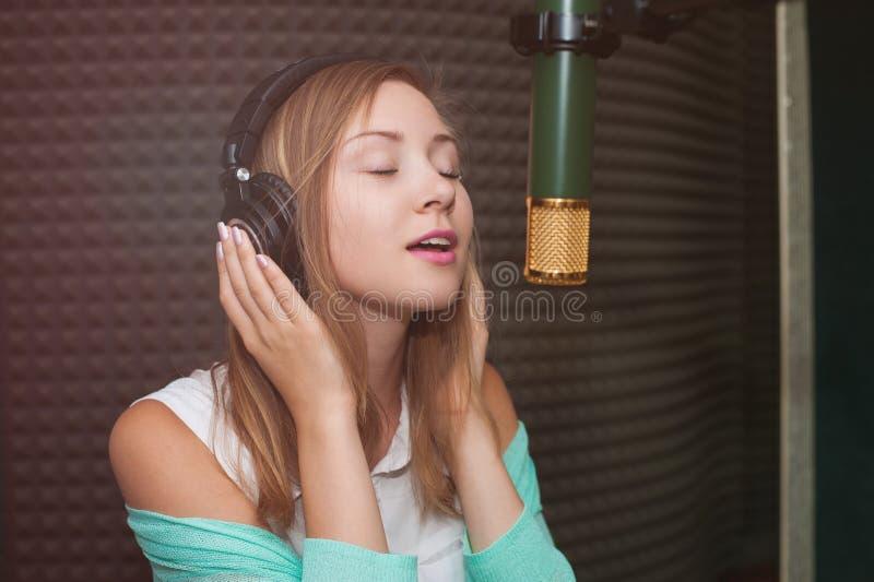 Ung kvinna som antecknar en sång i en yrkesmässig musikstudio arkivfoto