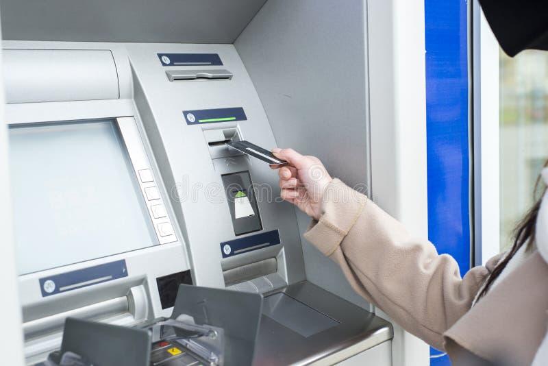 Ung kvinna som använder ATM arkivbilder