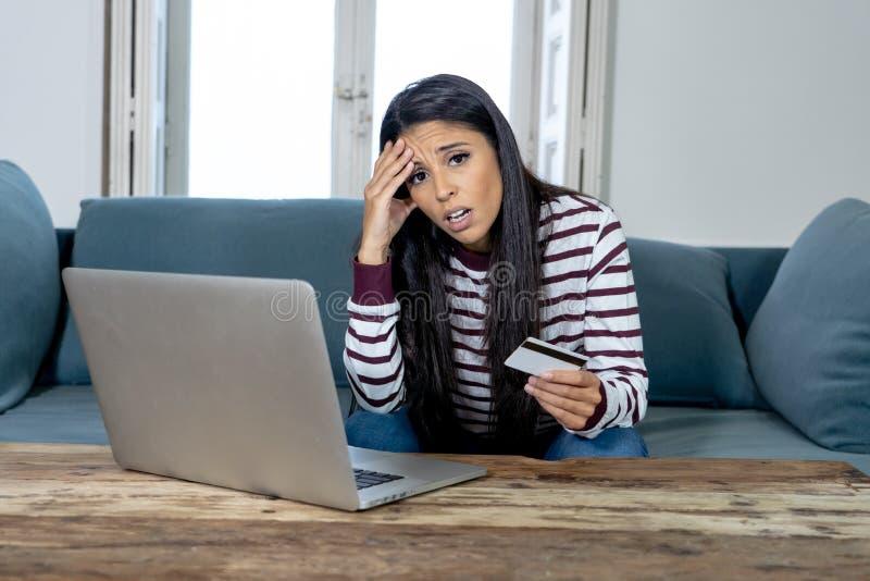 Ung kvinna som använder bärbara datorn som är ilsken och som är stressad om hennes kreditkorträkning royaltyfria foton