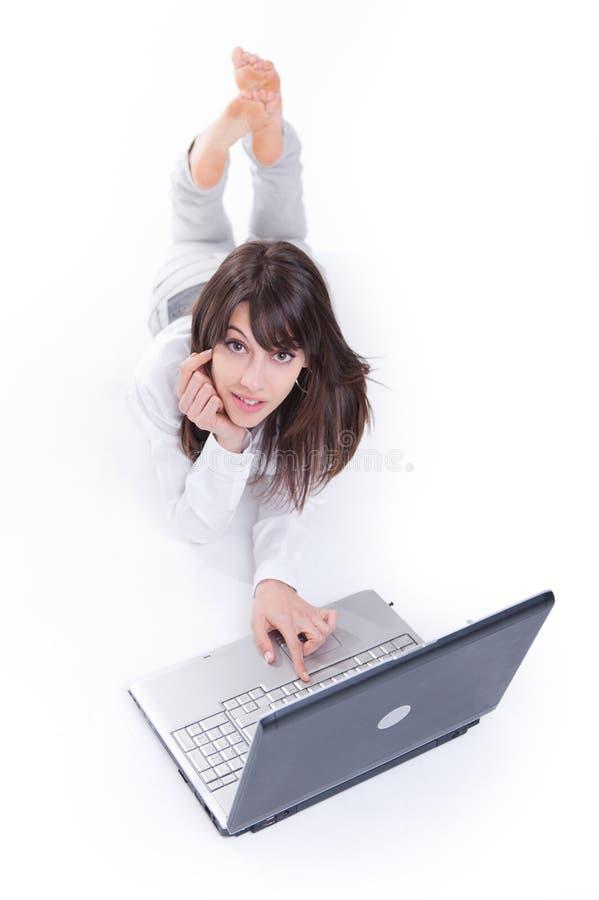 Ung kvinna som använder bärbara datorn arkivbilder