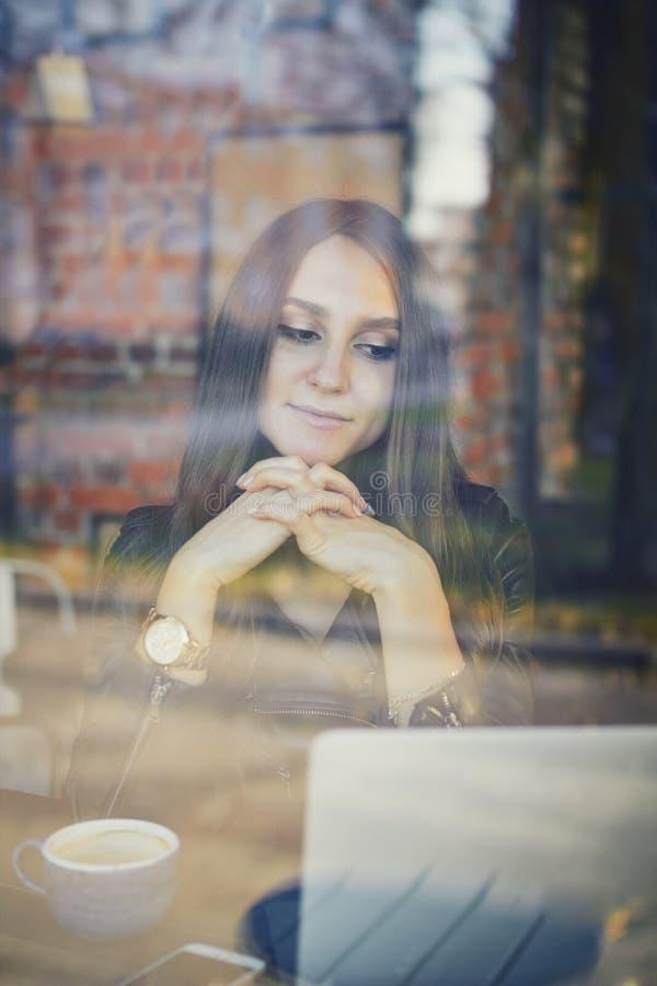 Ung kvinna som använder bärbara datorn i ett kafé Avlägset jobbbegrepp royaltyfri fotografi