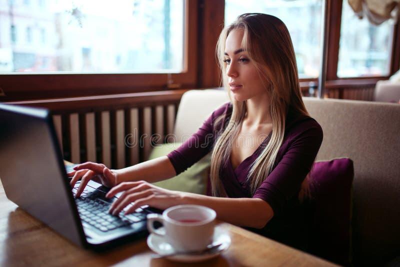 Ung kvinna som använder bärbara datorn i kafé arkivbilder