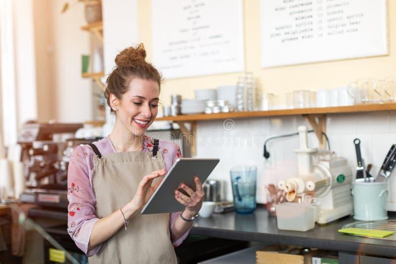 Ung kvinna som använder den digitala minnestavlan i coffee shop arkivbilder