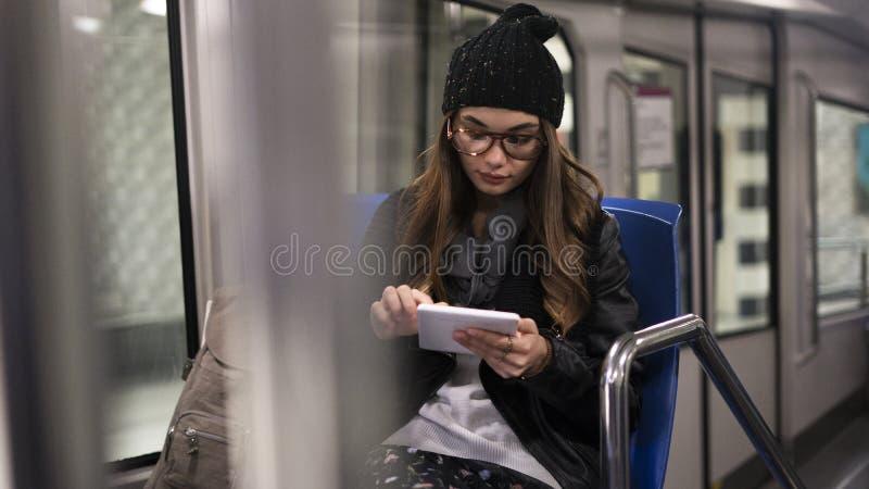 Ung kvinna som använder den digitala minnestavlan i tunnelbana royaltyfria foton