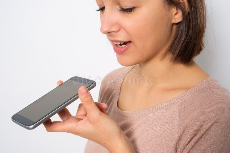 Ung kvinna som använder den röst- assistenten för telefon som isoleras på vit backgr arkivfoto