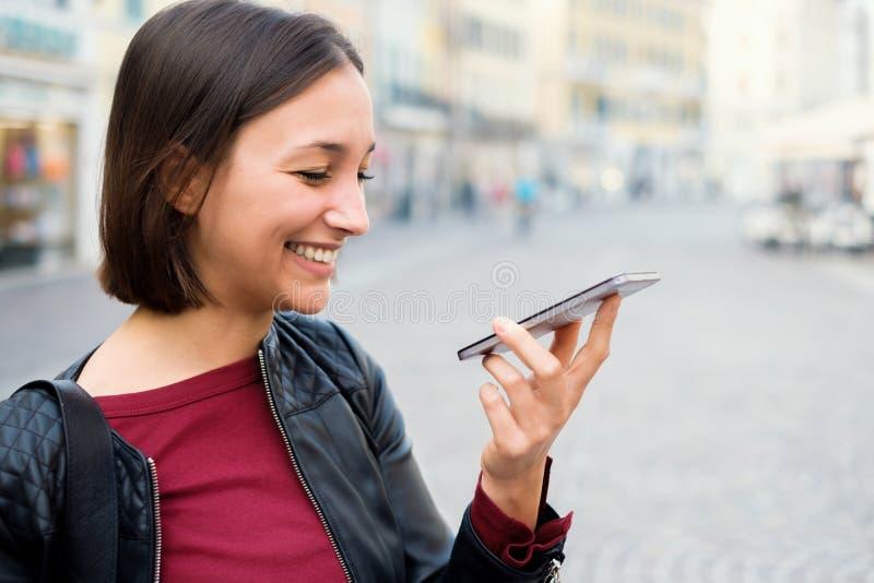 Ung kvinna som använder den röst- assistenten och överför det röst- meddelandet royaltyfri fotografi
