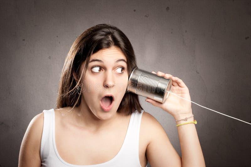 Ung kvinna som använder en can som telefonen royaltyfria foton