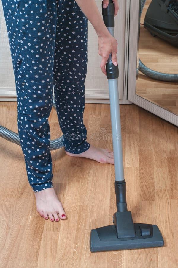 Ung kvinna som använder en dammsugare i sovrum svampar för flytande för cleaningbegreppsdishwashing royaltyfri bild