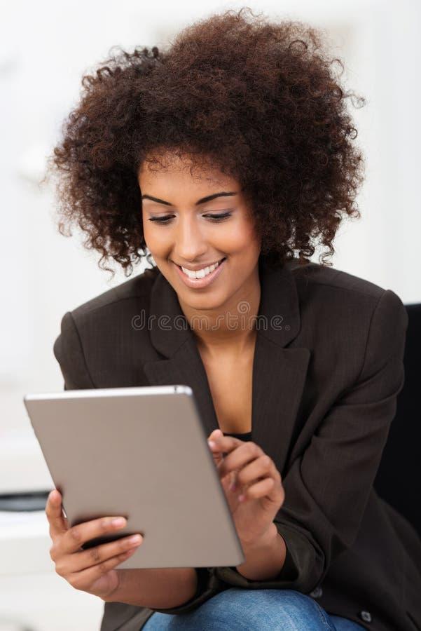 Ung kvinna som använder en innovativ minnestavlaPC arkivbild