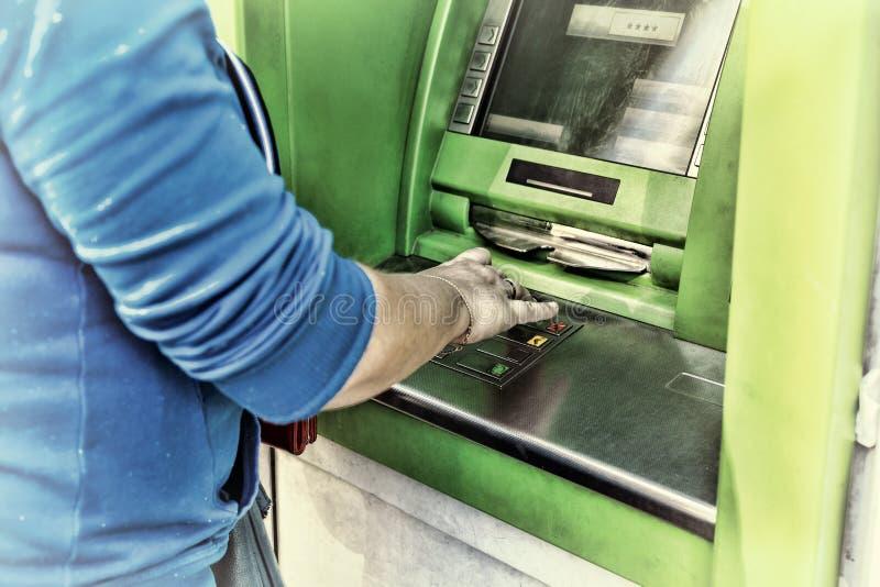 Ung kvinna som använder en kontant punkt Ung flicka som använder ATM royaltyfri foto
