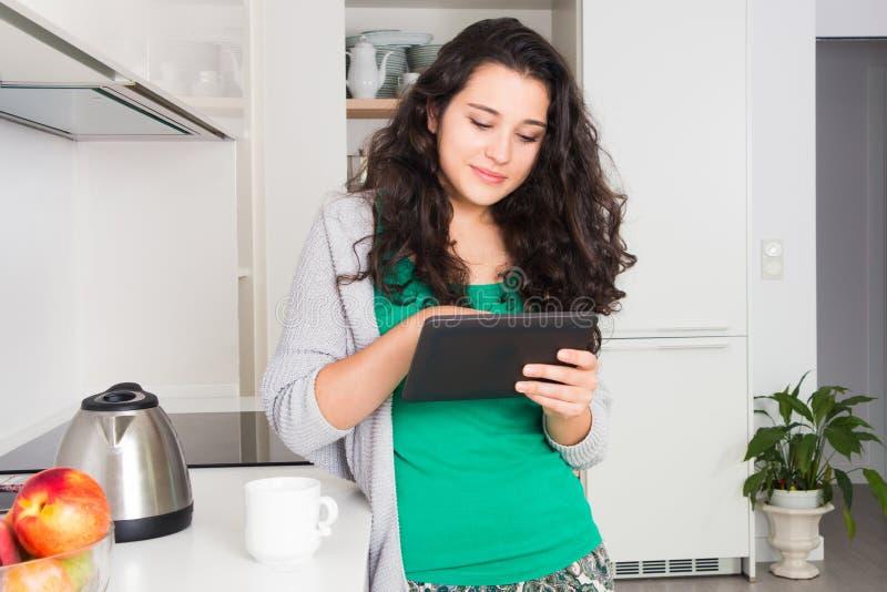 Ung kvinna som använder en minnestavla i hennes kök royaltyfri fotografi
