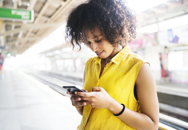 Ung kvinna som använder en smartphone royaltyfri foto