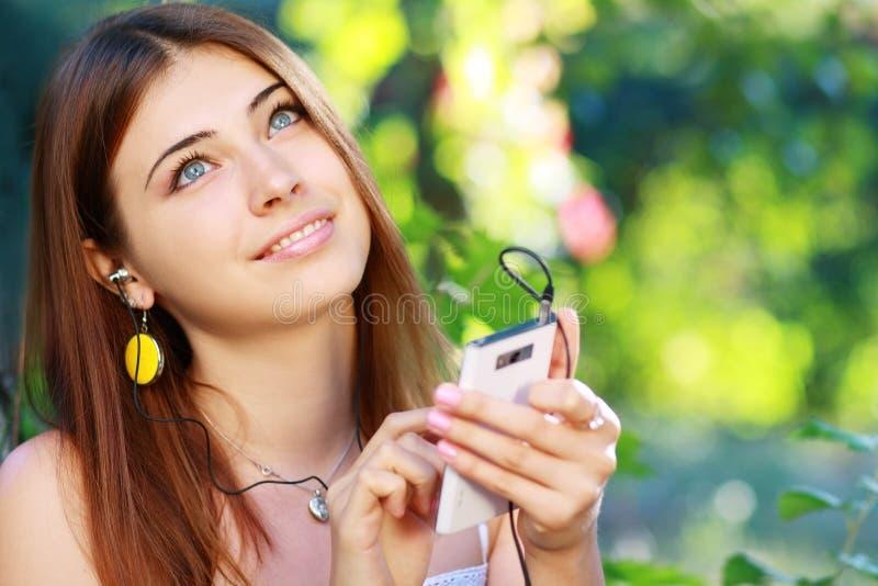 Ung kvinna som använder en smartphone för att lyssna till musik royaltyfri bild