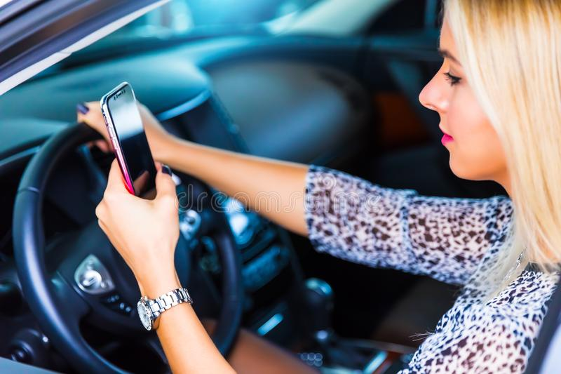 Ung kvinna som använder en smartphone, medan köra en bil arkivfoto
