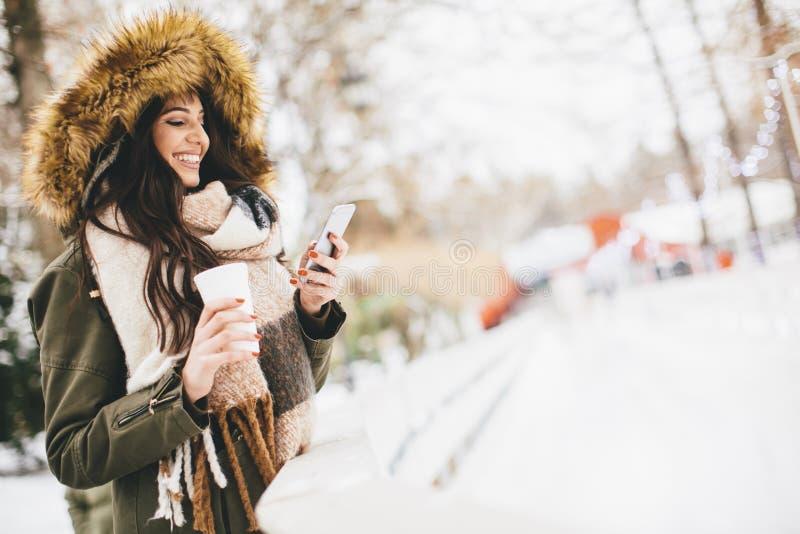 Ung kvinna som använder en telefon och dricker varmt te i vintermedeltalen royaltyfria foton