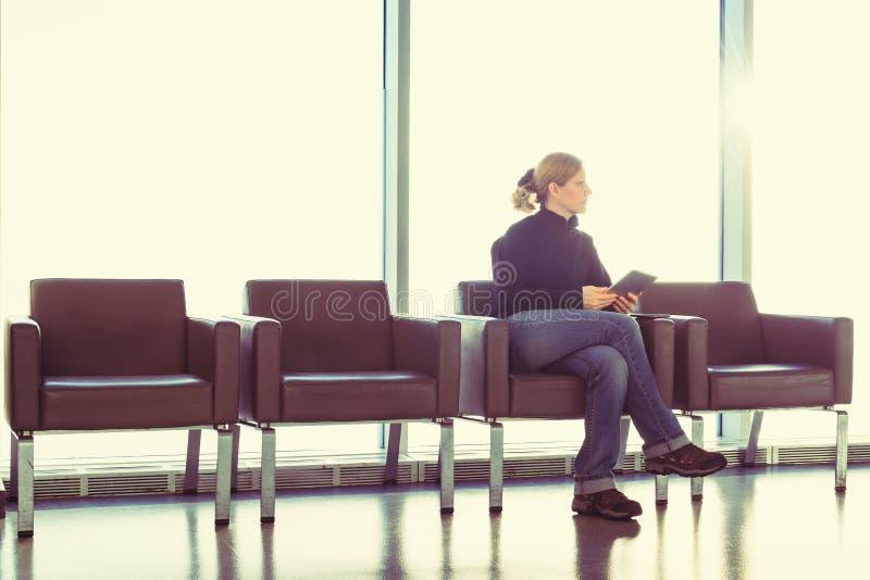 Ung kvinna som använder hennes digitala minnestavlaPC på en flygplatsvardagsrum, modernt väntande rum, med panelljuset arkivfoto