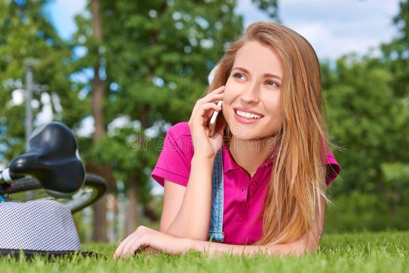 Ung kvinna som använder hennes smarta telefon på parkera arkivbilder