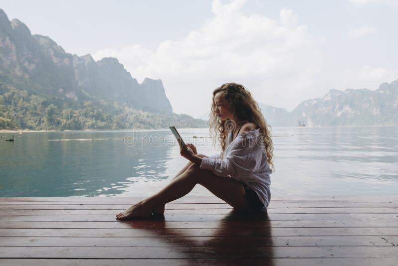 Ung kvinna som använder hennes telefon vid en sjö arkivfoto
