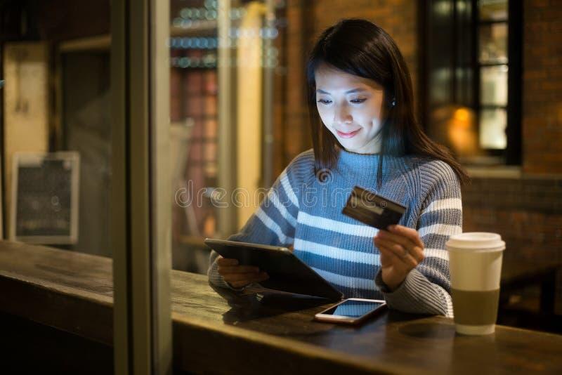 Ung kvinna som använder kreditkorten för att betala på minnestavlan royaltyfri foto