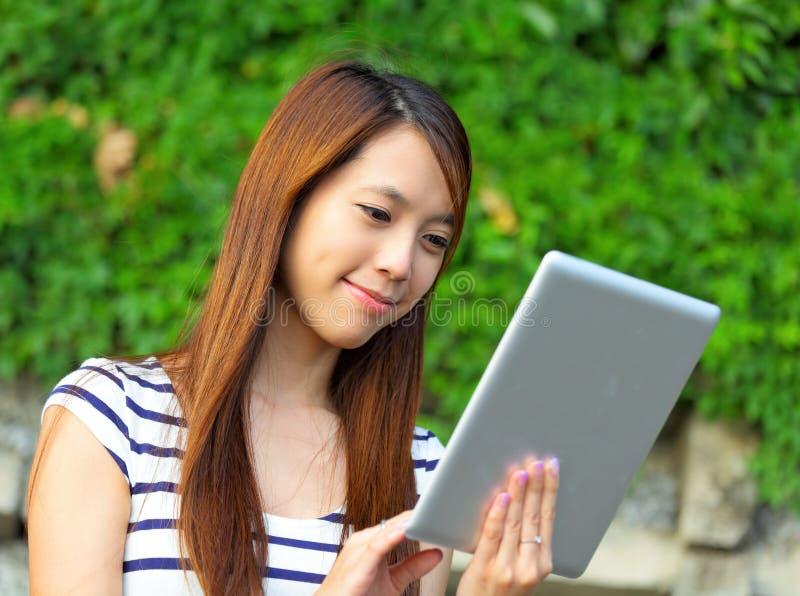 Ung kvinna som använder minnestavlan arkivbild
