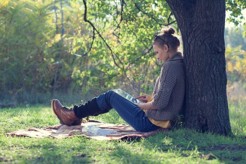 Ung kvinna som använder minnestavlaPC fotografering för bildbyråer
