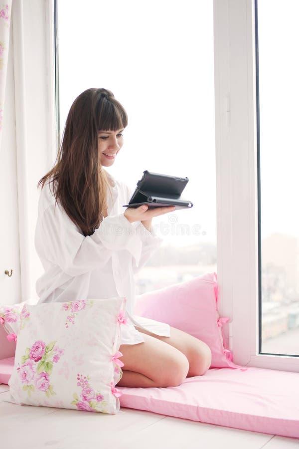 Ung kvinna som använder minnestavlaPC arkivfoto