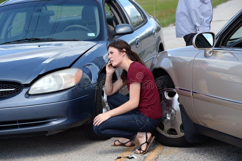 Ung kvinna som använder mobiltelefonen efter olycka royaltyfria bilder