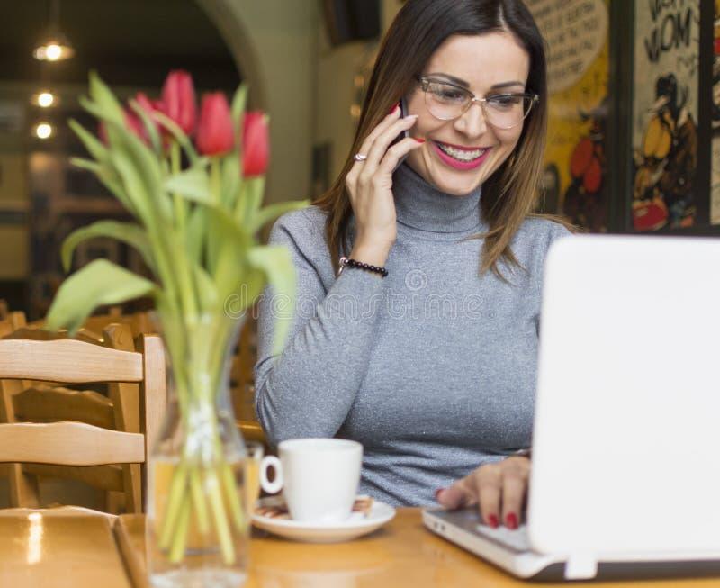 Ung kvinna som använder mobiltelefonen i coffee shop royaltyfri bild