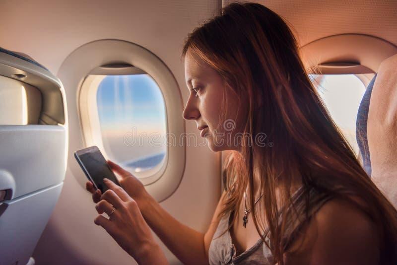 Ung kvinna som använder mobiltelefonen i flygplan på solnedgången arkivbilder