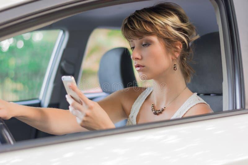 Ung kvinna som använder mobiltelefonen, medan köra en bil royaltyfri foto