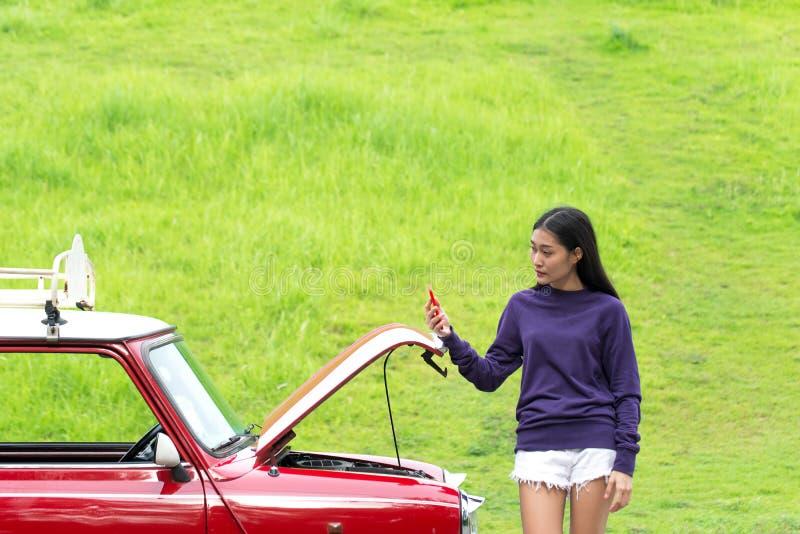 Ung kvinna som använder mobiltelefonen, medan se den brutna ner bilen arkivbild