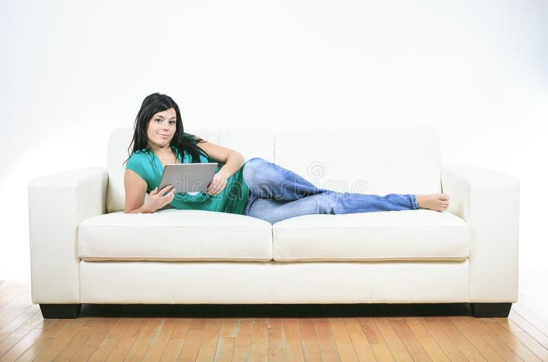 Ung kvinna som använder på elektroniskt minnestavlasammanträde royaltyfri foto