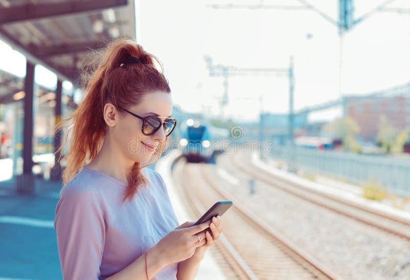 Ung kvinna som använder sin mobiltelefon på tunnelbaneplattform, kontrollerar meddelanden via sms-mail eller tågschema arkivfoton