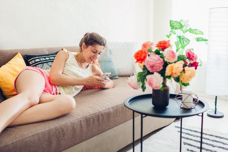 Ung kvinna som använder smartphonen som hemma ligger på soffan Vardagsrum som dekoreras med buketten av rosor royaltyfri bild